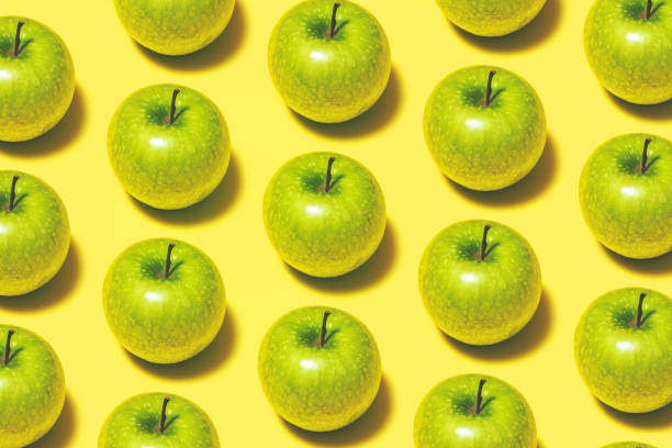Green apple repetitive flat lay on yellow background stock photo