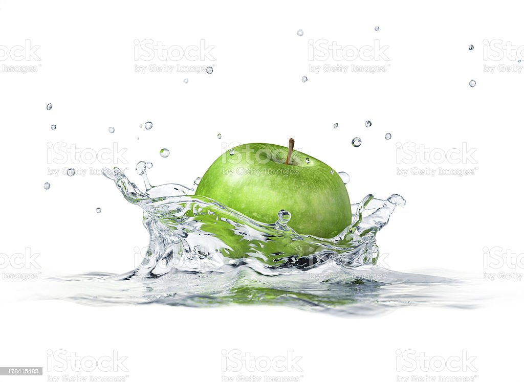 Green apple splashing into water. Close-up side view. stock photo