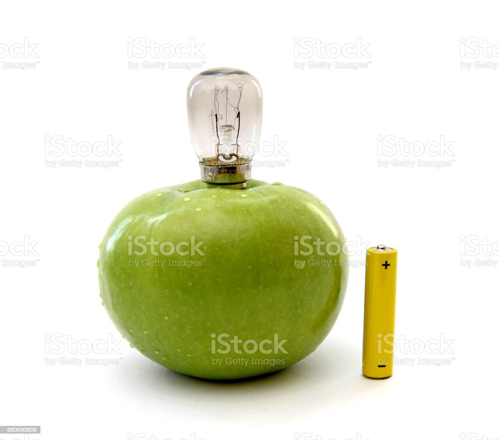 Green apple with a lamp and a battery stock photo