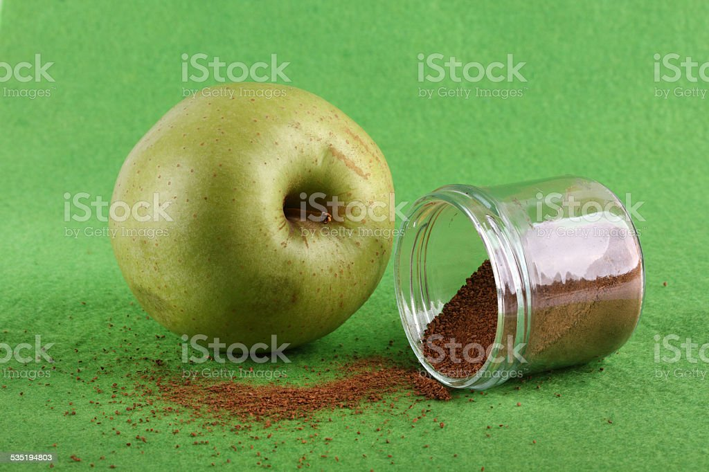 Green apple with cinnamon stock photo