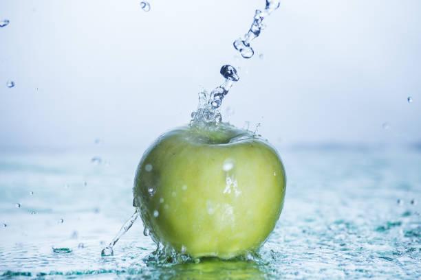 Grüner Apfel mit gefriertem Wasserspritzer – Foto