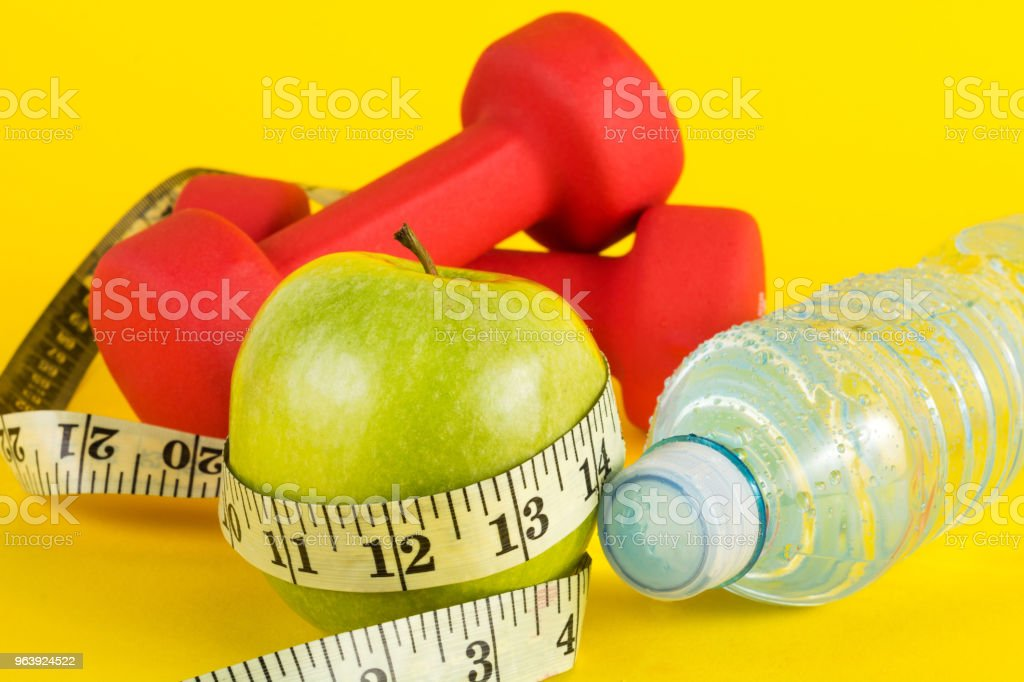 Green apple with measuring tape, red dumbbell and fresh water bottle with drops on yellow - Royalty-free Adhesive Tape Stock Photo