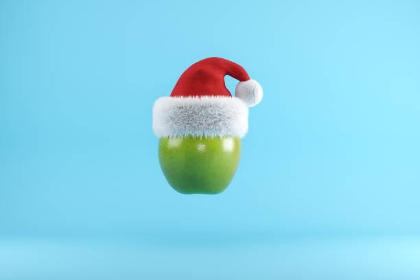 Grüner Apfel mit Santa Hut schwimmen auf blauem Hintergrund, Weihnachten Obst Konzept Ideen, 3D-Illustration. – Foto