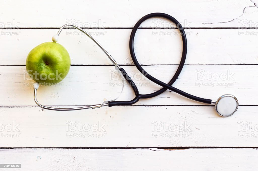 green apple with stethoscope on white wood table,Concept for diet, healthcare, nutrition or medical insurance stock photo