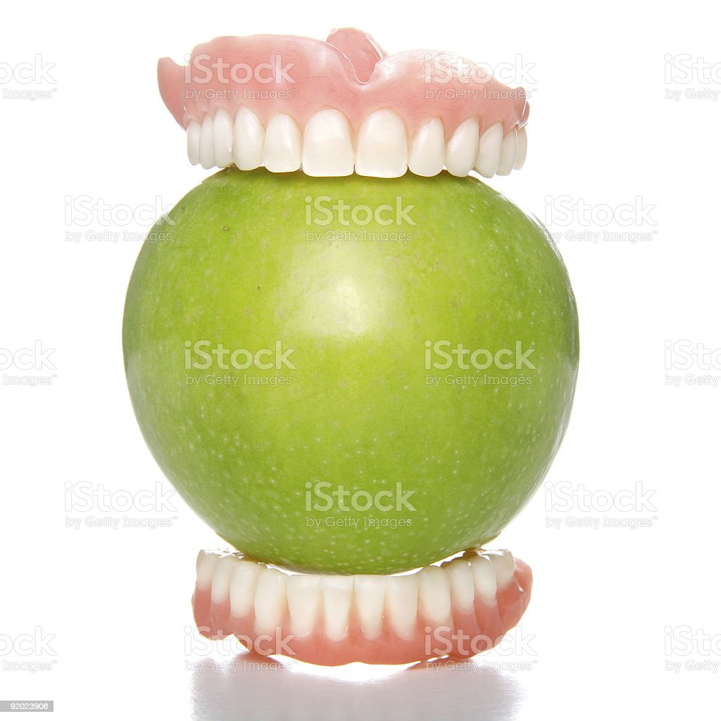 Green apple with top and bottom rows of teeth on either side stock photo
