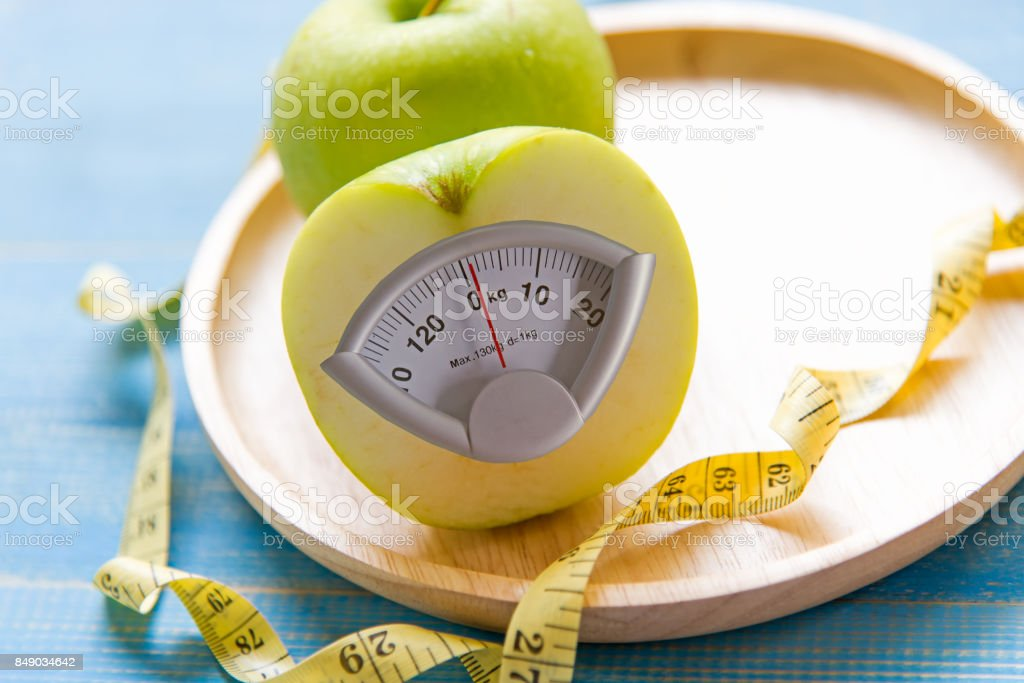 Green apple with weight scale and measuring tape for the healthy diet slimming . Diet and Healthy Concept stock photo
