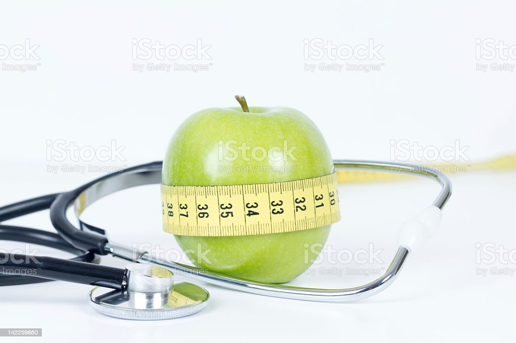Green Apple Wrapped with Measure Tape and Stethoscope stock photo