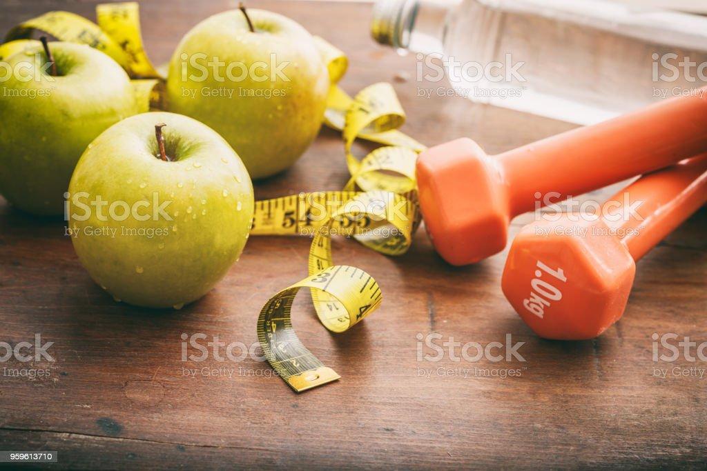 Manzanas verdes, pesas y cinta métrica en el fondo de madera - Foto de stock de Agua libre de derechos