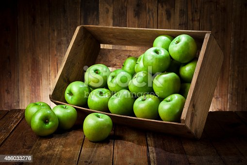Side view of a tilted wooden crate filled with fresh organic green apples sitting on rustic wood table. The crate is tilted with some apples out of it.Predominant color is brown and green. Low key DSRL studio photo taken with Canon EOS 5D Mk II and Canon EF 24-105mm f/4L IS USM Lens