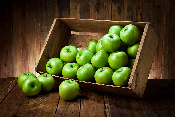 Green apples in a crate on rustic wood table Side view of a tilted wooden crate filled with fresh organic green apples sitting on rustic wood table. The crate is tilted with some apples out of it.Predominant color is brown and green. Low key DSRL studio photo taken with Canon EOS 5D Mk II and Canon EF 24-105mm f/4L IS USM Lens granny smith apple stock pictures, royalty-free photos & images
