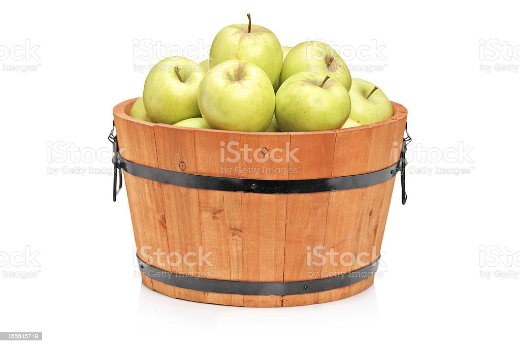Green apples in a wooden barrel stock photo
