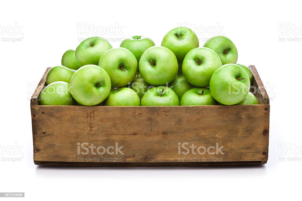 Green apples in a wooden crate isolated on white background stock photo