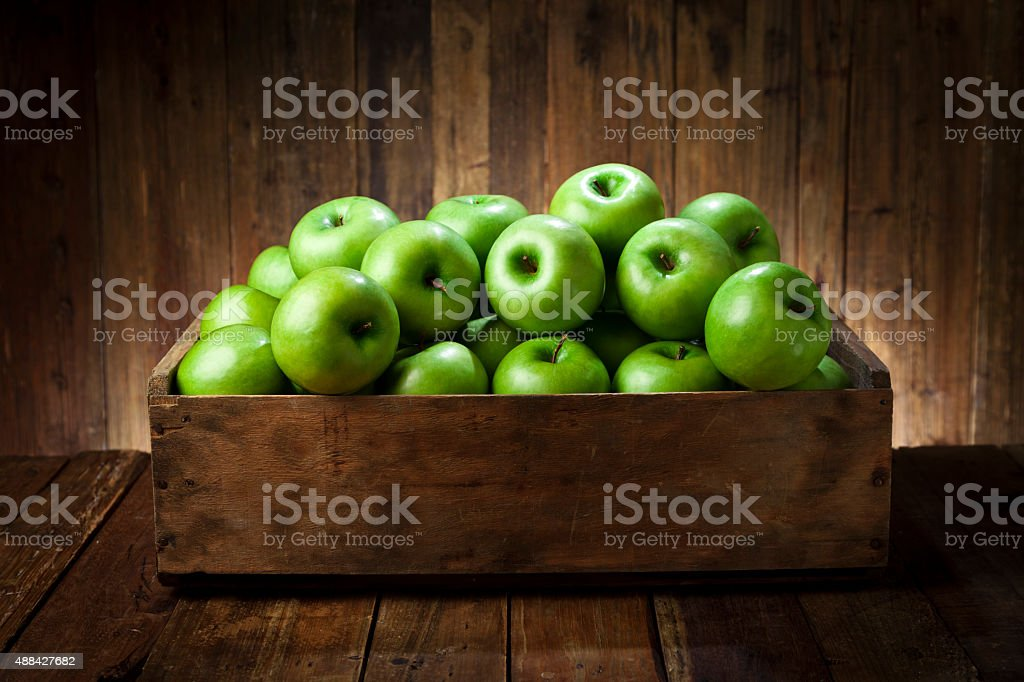 Green apples in a wooden crate on rustic wood table stock photo