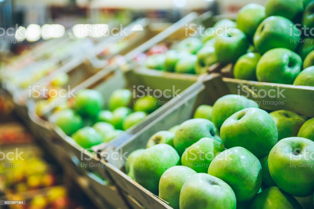 green apples in boxes on market shelves. grocery shopping concept. healthy food. stock photo