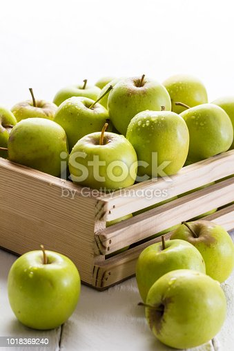 istock Green apples in crate close up on white background with selective focus 1018369240