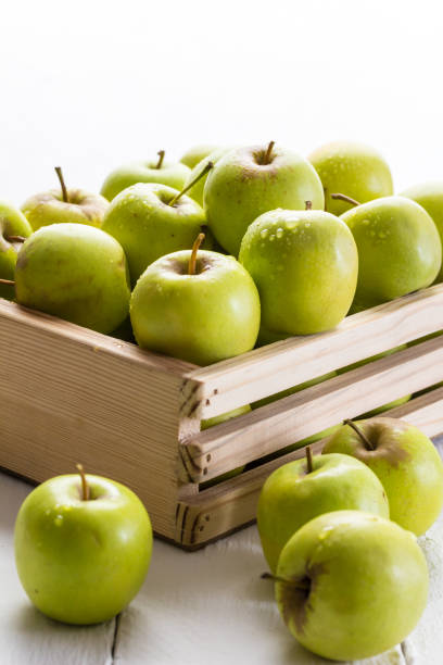pommes vertes dans la caisse bouchent sur fond blanc avec mise au point sélective - golden photos et images de collection