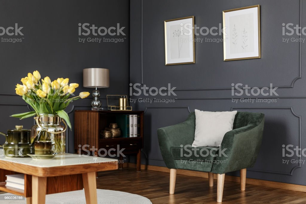 Green armchair against grey wall with posters in modern living room...