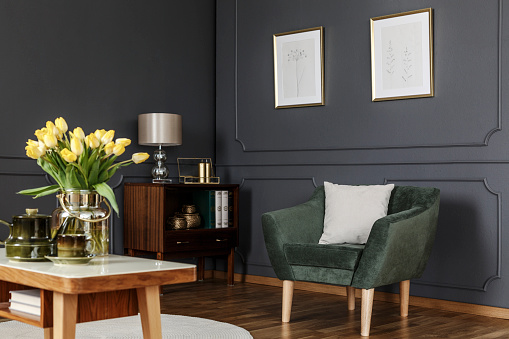 Green armchair against grey wall with posters in modern living room interior with flowers