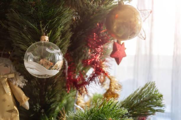 Arbre artificiel vert de Noel décoré avec la boule transparente avec les modèles blancs et d'or et d'autres jouets pour des vacances de famille. Mise au point sélective - Photo