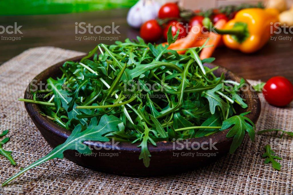 Green arugula leaves in bowl. Fresh salad. royalty-free stock photo