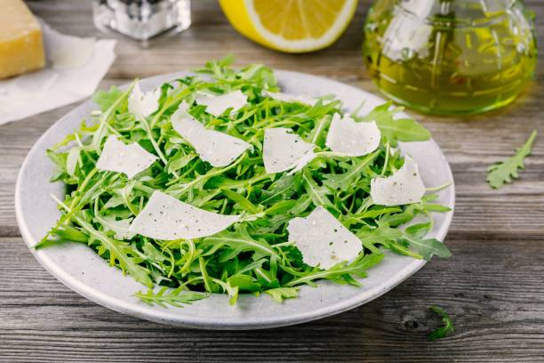 파 르 마 치즈, 레몬, 올리브 기름 및 조미료와 녹색 arugula 샐러드 - 아루굴라 뉴스 사진 이미지