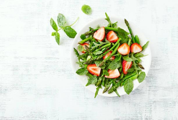 grüner spargel und erdbeer-salat mit rucola, minze und zitrone-honig-dressing - spargel vegan stock-fotos und bilder