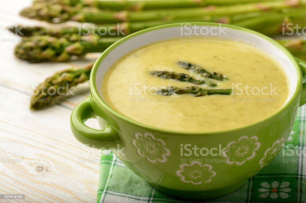 Green asparagus cream soup on wooden background. stock photo