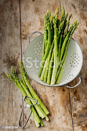 Overhead view of an arrangement of freshly picked green asparagus, photographed against a rustic wooden background. Colour, vertical with some copy space.