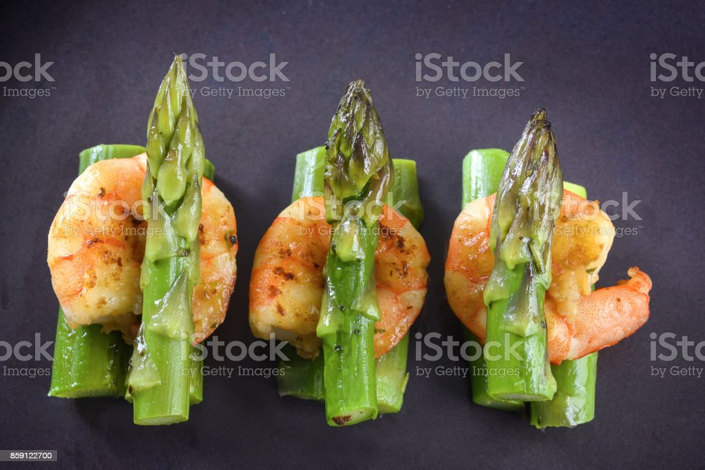 green asparagus with tiger prawn shrimp, close up top view from above, festive appetizer or buffet snack on a gray plate stock photo