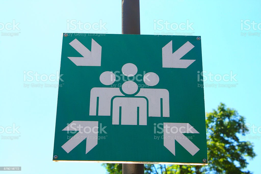 Green assembly point sign on street stock photo