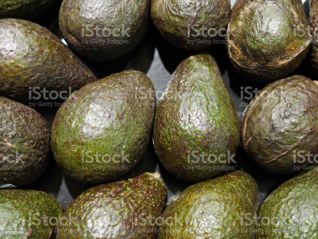 Green Avacados stacked at farmers' market stock photo