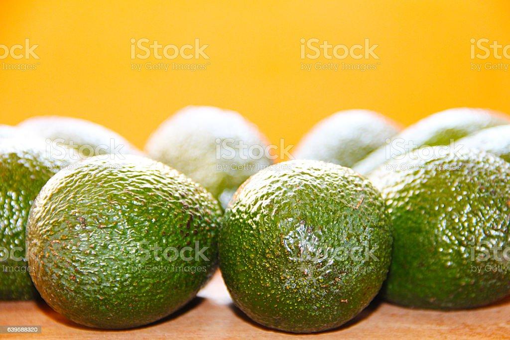 Green avocado on wooden board on an orange background stock photo