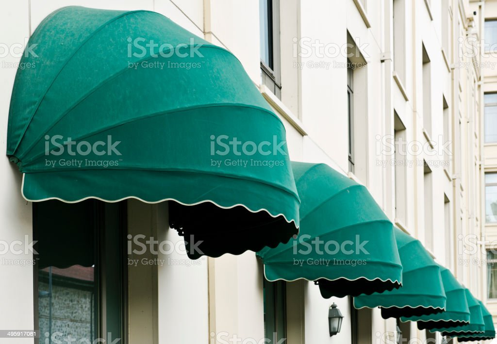 Green Awnings Over Windows in Hotel Wall stock photo