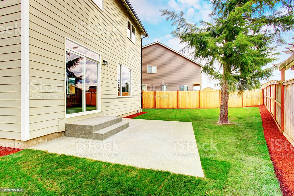 Green back yard of American tow level beige house with small concrete...