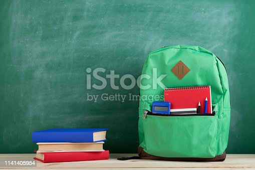 istock green backpack, calculator, books and notebooks on the background of the blackboard 1141405954