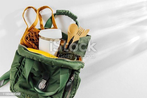 Green backpack with mesh market bag, bamboo cutlery  and  reusable coffee mug. Sustainable lifestyle. Zero waste, plastic free concept.