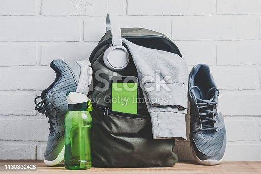 istock Green backpack with sportswear and sneakers. The concept of fitness or running 1130332428