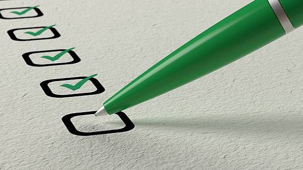 Green ball pen crossing off items from a checklist stock photo