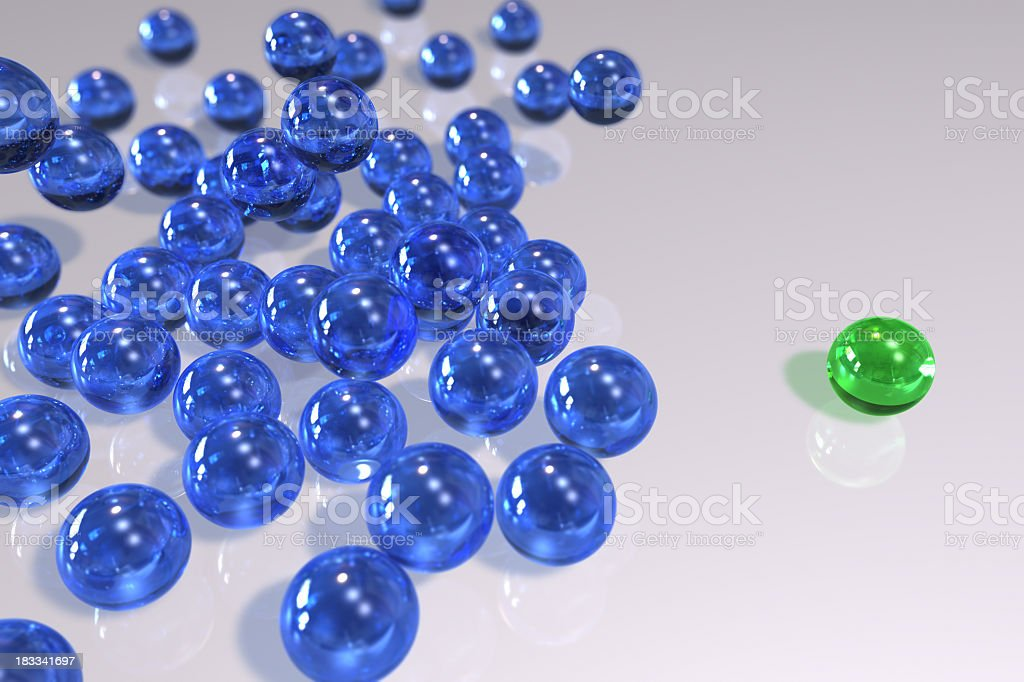 A green ball that stands out from the crowd of blue balls royalty-free stock photo