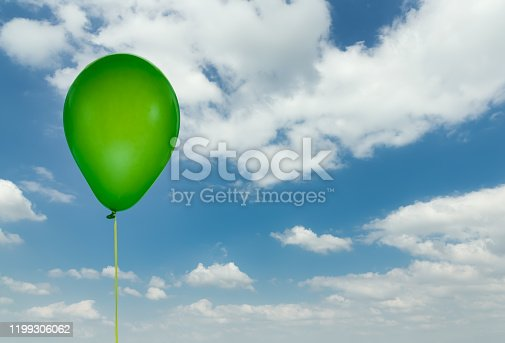 1141701990 istock photo Green balloon isolated at blue sky with clouds 1199306062