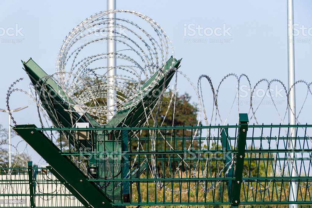 green barb wire fence stock photo