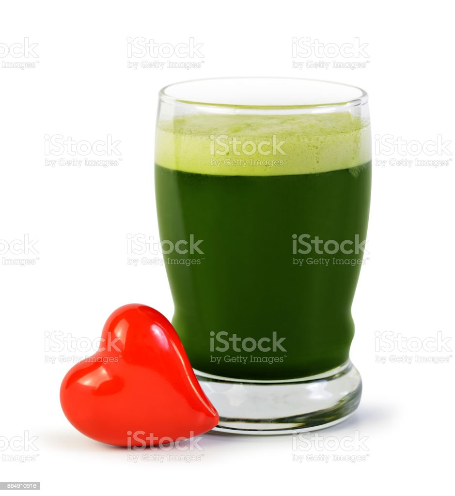 Green barley juice drink in glass and red heart. stock photo