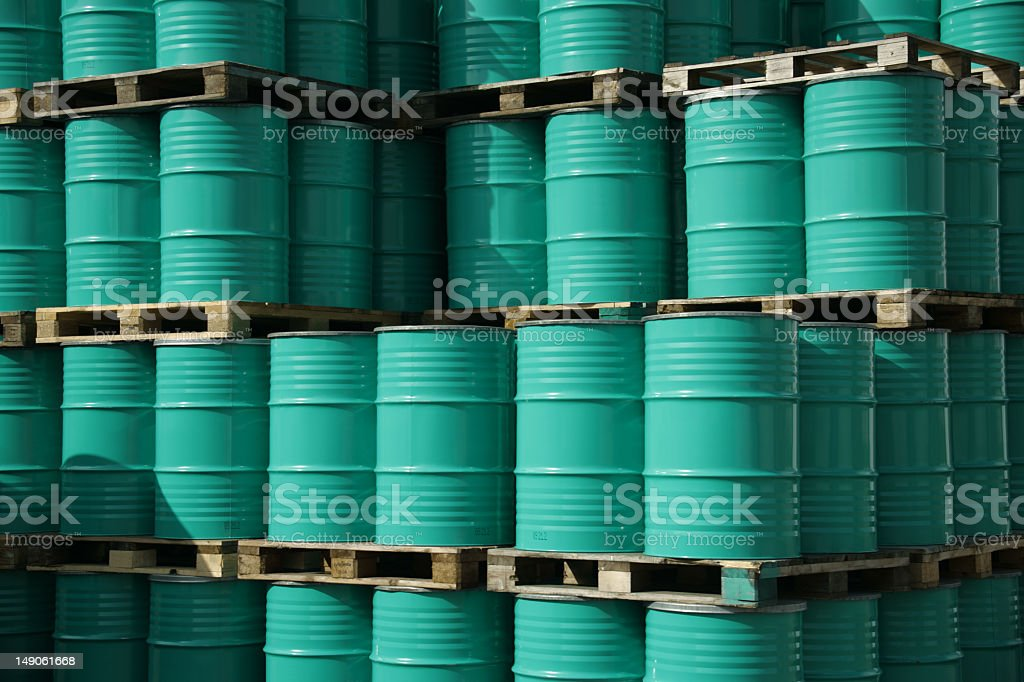 Green barrels stacked high filled with oil stock photo