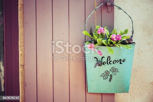 loseup of green basket with fresh flowers and welcome sign text written in black on wall near door