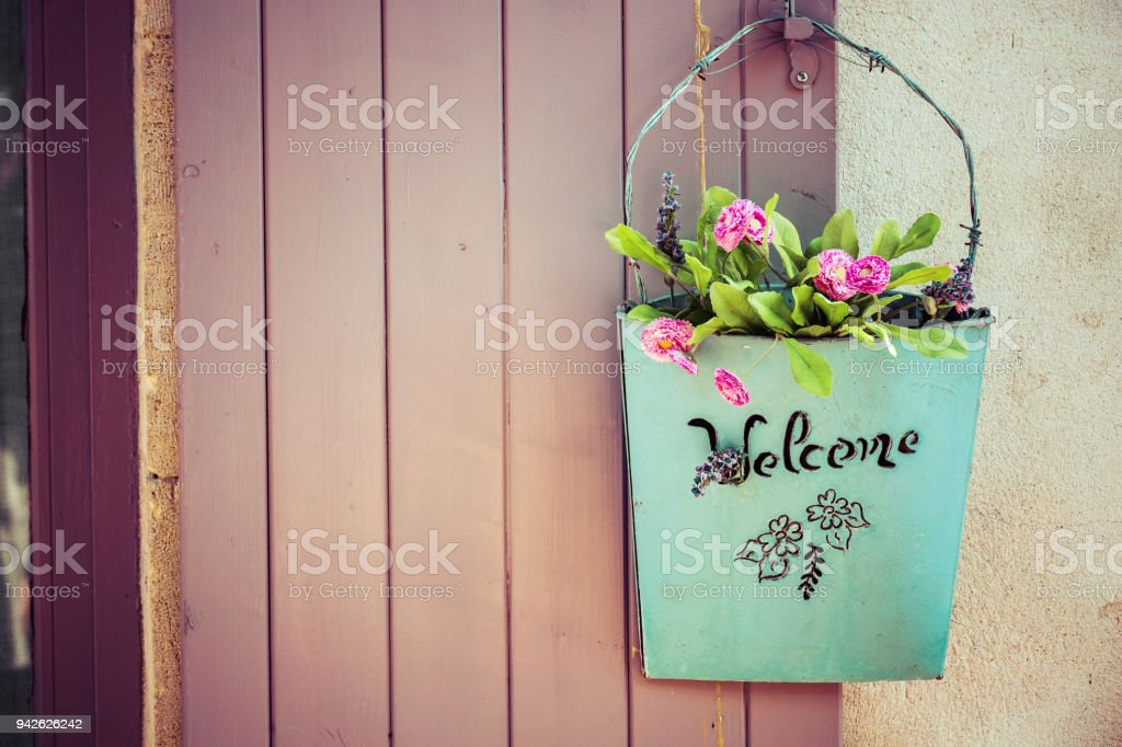 Green basket with welcome and flower stock photo