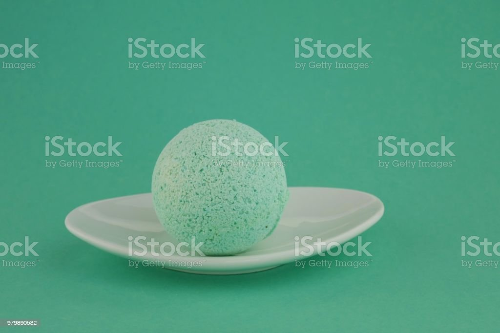 green bath bomb with herbs extract. bath bomb in a white plate on a green background. Natural Herbal Cosmetics stock photo