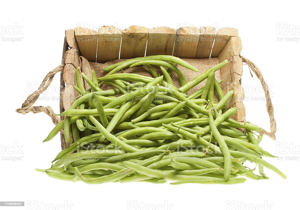 Green beans coming out of a wooden basket stock photo