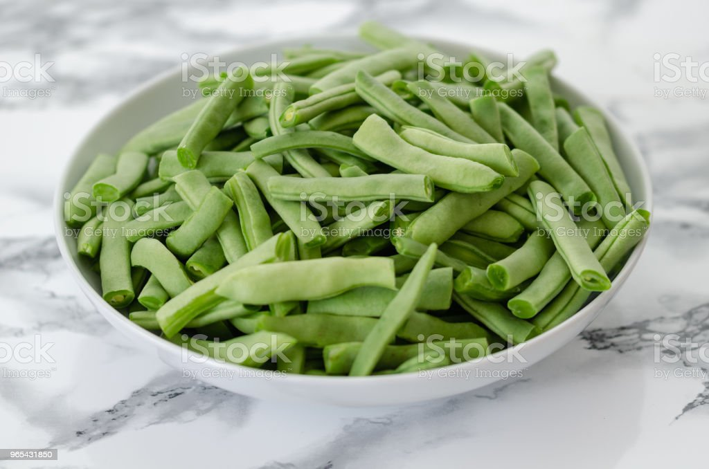Green beans in the white plate on  grey and white background.ready to cook. royalty-free stock photo