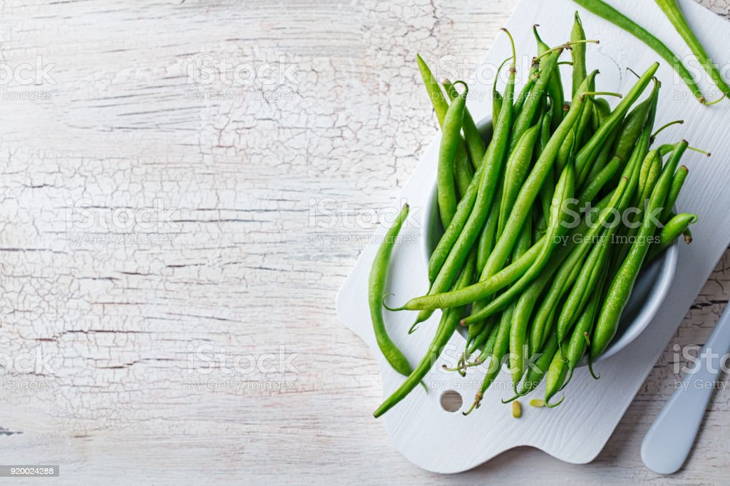 Green beans in white bowl on cutting board. Top view. Copy space stock photo