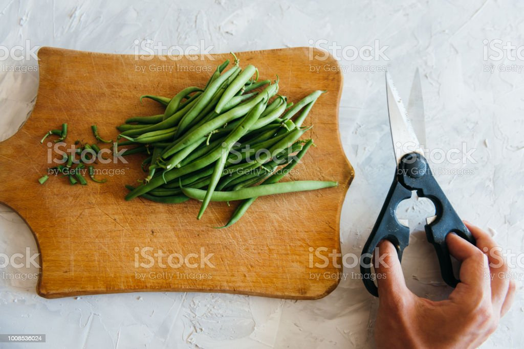 Green Beans on a grey concrete background wooden board cutting with scissors stock photo